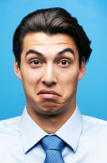 Stock Photo: 4197R-58979 Young businessman with a digusted and confused expression