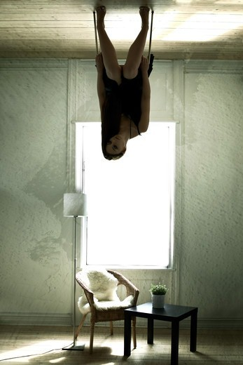 Bizarre image of a young woman sitting upside-down on a chair on her ceiling : Stock Photo