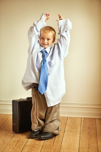 Portrait of a young boy wearing his dad's work clothes and holding a suitcase : Stock Photo