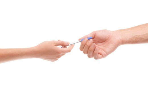 Stock Photo: 4197R-59450 Cropped view of a female hand passing a male hand a pen