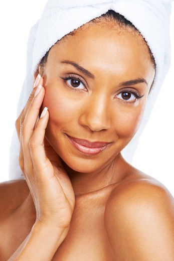 Stock Photo: 4197R-59696 A beautiful african american woman enjoying the feel of her smooth skin after a spa treatment