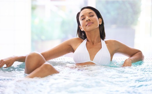 A young ethnic woman sitting in a jacuzzi with her eyes closed : Stock Photo