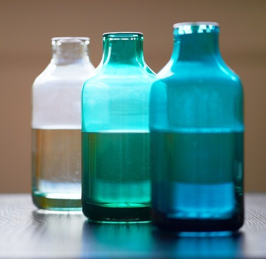 Stock Photo: 4197R-59853 Three jars of differing colour containing water and beauty oils in a receding line - Spa Arrangement