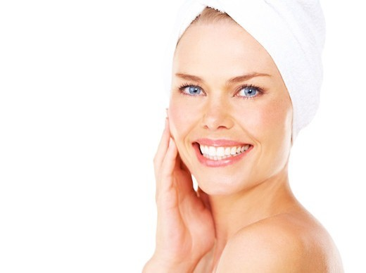 Stock Photo: 4197R-59882 Smiling young blonde woman with a towel wrapped around her head against a white background