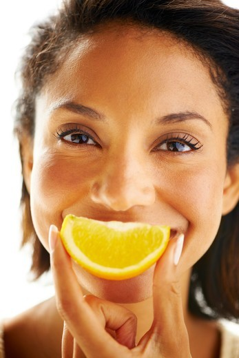Stock Photo: 4197R-60041 Portrait of an attractive woman holding up an orange wedge in front of her mouth