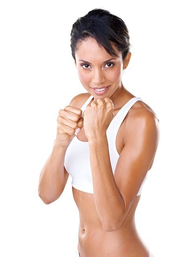 Beautiful young woman with her fists raised against a white background in a fighter's stance : Stock Photo