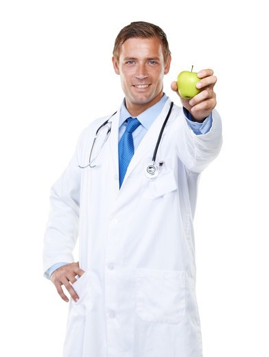 Stock Photo: 4197R-60290 Studio portrait of a confident young doctor holding an apple towards the camera isolated on white