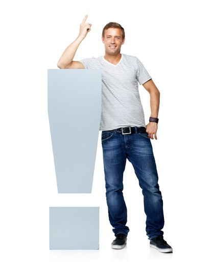 Stock Photo: 4197R-60357 An casual young man pointing upwards while standing next to an exclamation mark