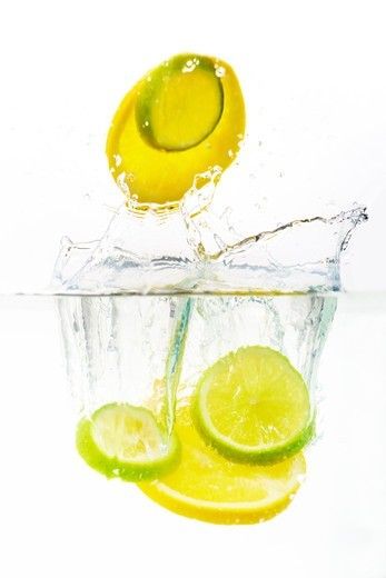 Stock Photo: 4197R-60638 Studio shot of lemon and lime slices being dropped into clear water