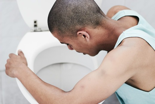 Stock Photo: 4197R-60853 A young drug addict vomiting in the toilet after a drug binge