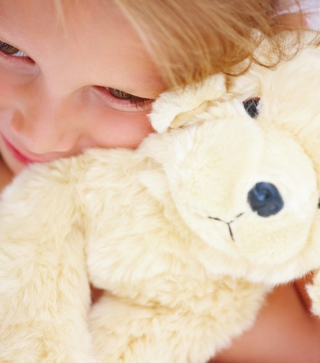 Closeup portrait of a cute girl holding soft toy : Stock Photo