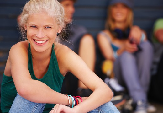 Portrait of a happy young girl with friends in background : Stock Photo