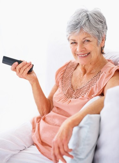 Portrait of a smiling elderly woman holding the television remote : Stock Photo