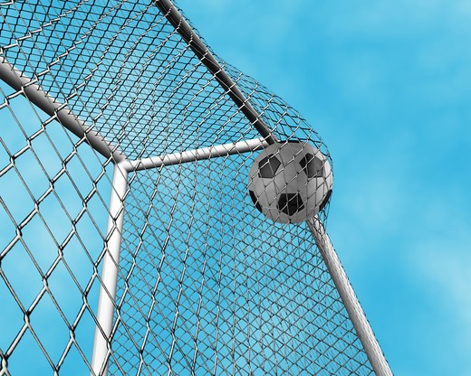 3D render of a football going into the net : Stock Photo
