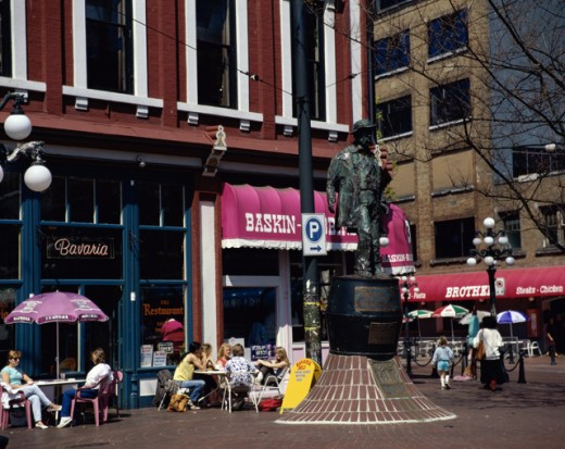 Tourists sitting at a sidewalk cafe, Gassy Jack Statue, Gastown, Vancouver, British Columbia, Canada : Stock Photo