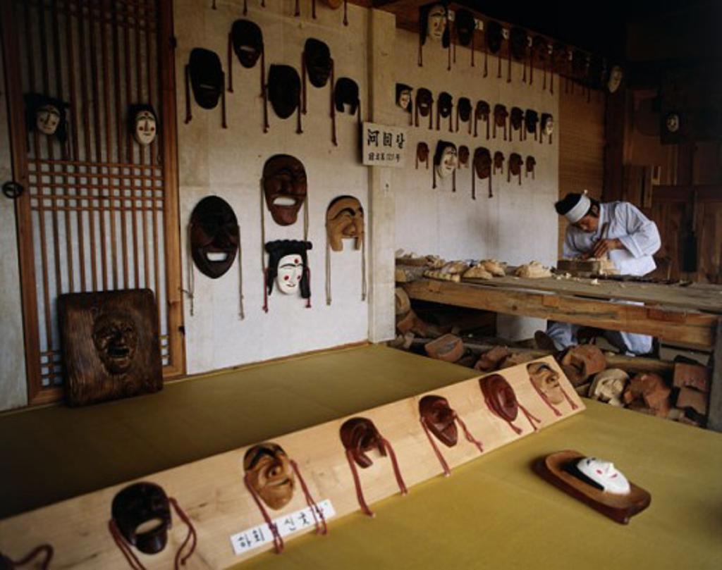 Mid adult man working on wooden masks, Korean Folk Village, Seoul, South Korea : Stock Photo