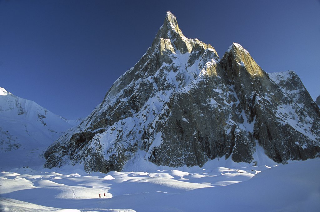 Skiers under rock spire, unnamed peak near Concordia, Baltoro Glacier, Karakoram Mountains, Pakistan : Stock Photo