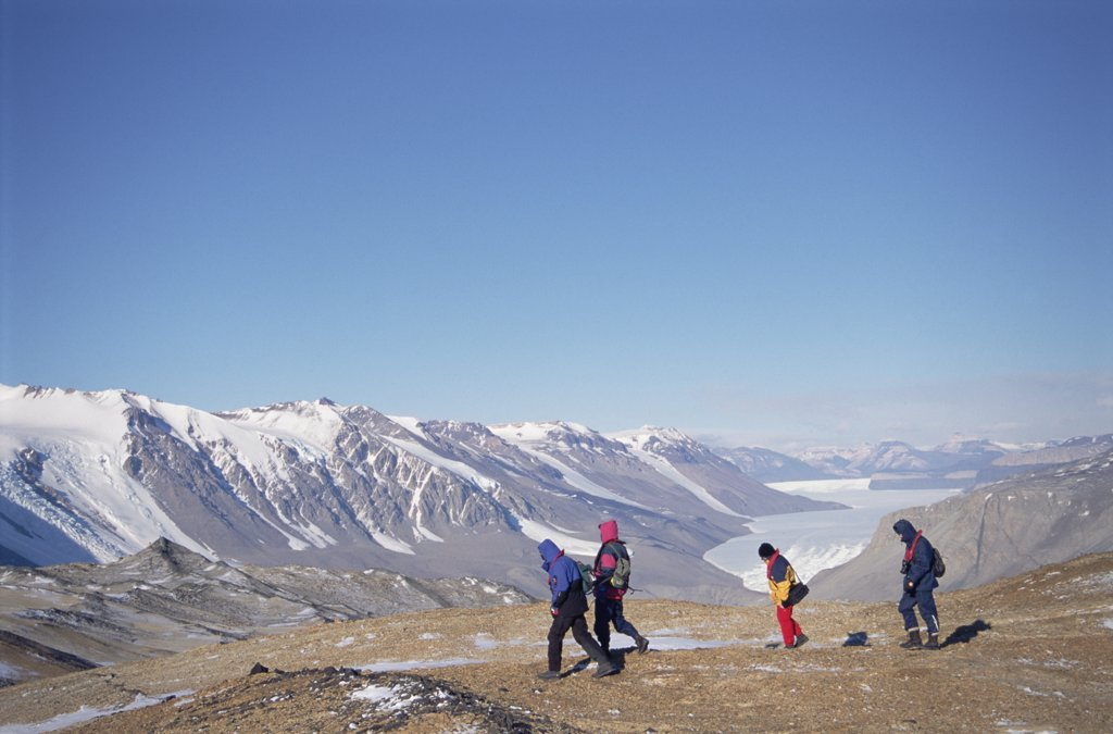 Tourists in frozen desert sheltered by Asgard Range, Taylor Dry Valley, Ross Sea, Antarctica : Stock Photo