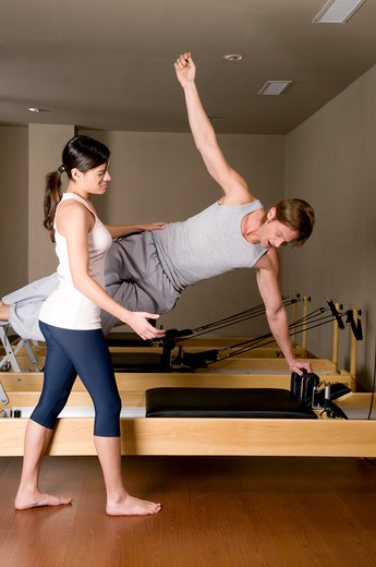 Stock Photo: 4202R-188 Young woman assisting a young man in exercise