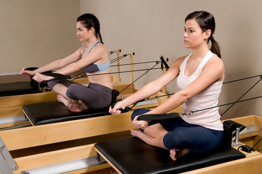 Two young women working out with Pilates exercise machine in a gym : Stock Photo