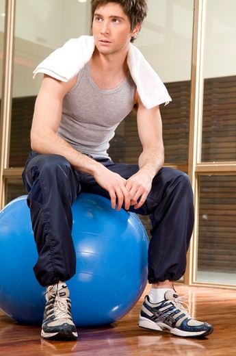 Stock Photo: 4202R-206 Young man sitting on a fitness ball