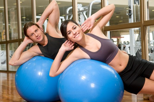 Stock Photo: 4202R-216 Young couple exercising on fitness balls