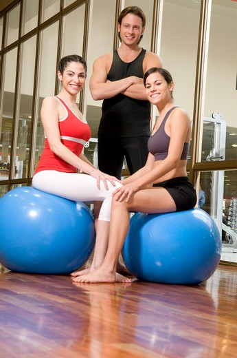 Stock Photo: 4202R-217 Two young women sitting on fitness balls with their trainer standing near them