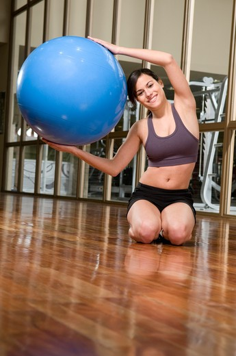 Stock Photo: 4202R-224 Young woman exercising with a fitness ball in a gym
