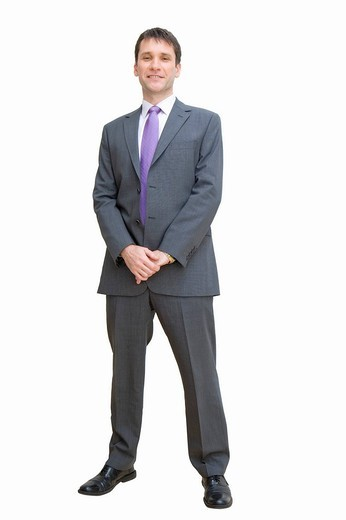 Confident businessman standing with hands clasped : Stock Photo