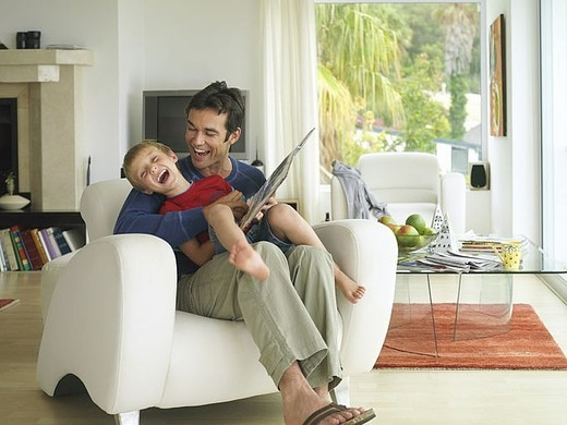 Stock Photo: 4208R-10161 Father and son 5-7 looking at photo album at home, boy in father´s lap in armchair, laughing