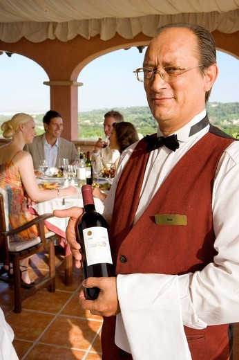 Waiter holding wine bottle with well_dressed couples dining in background : Stock Photo