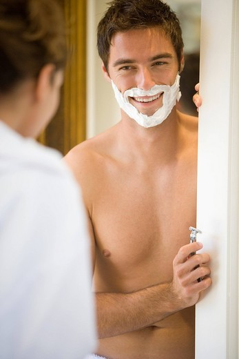 Stock Photo: 4208R-1029 Man preparing to shave, smiling at woman differential focus