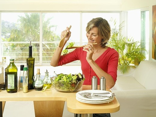 Woman tossing salad with olive oil and balsamic vinegar dressing in bowl in kitchen, smiling : Stock Photo