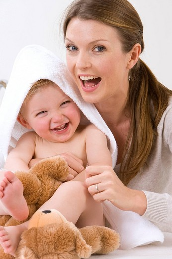 Mother hugging laughing baby boy with towel on head : Stock Photo
