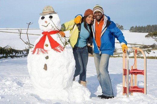 Stock Photo: 4208R-10447 Couple with snowman and sled in snowy field