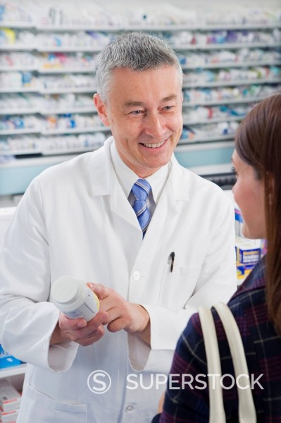 Pharmacist explaining medicine instructions to customer in pharmacy : Stock Photo