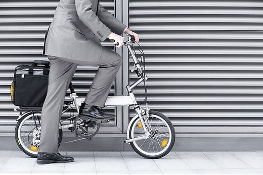 Stock Photo: 4208R-10551 Businessman cycling on folding commuter bicycle on pavement, side view, low section