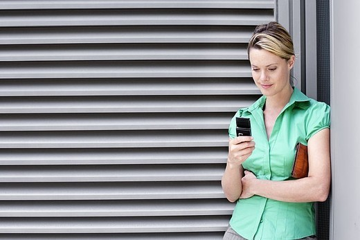 Young woman in green short-sleeved blouse text messaging on mobile phone : Stock Photo