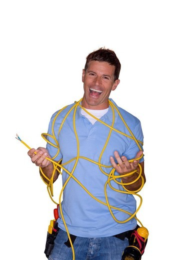 Stock Photo: 4208R-10598 Laughing handyman tangled in electrical wire