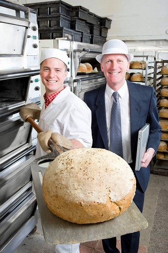 Inspector with baker as he removes bread from oven : Stock Photo