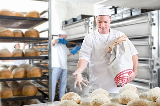 Baker sprinkling loaves of bread with flour : Stock Photo