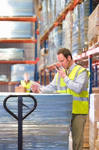 Warehouse manager using walkie_talkie and viewing paperwork on pallet truck : Stock Photo