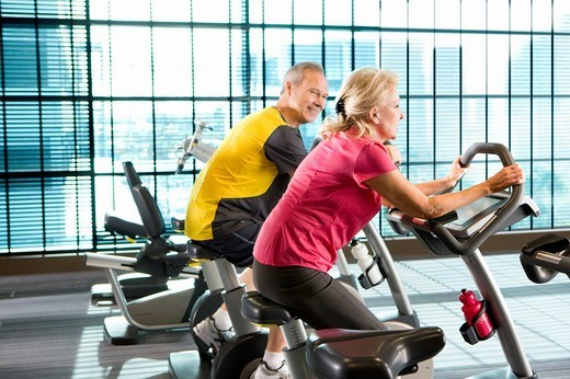 Couple riding exercise bikes in health club : Stock Photo