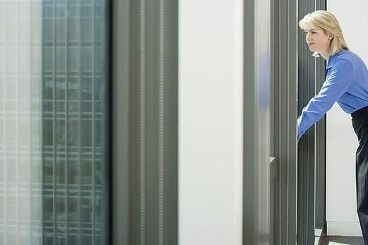 Businesswoman leaning against window sill in office, looking through window, smiling, side view : Stock Photo