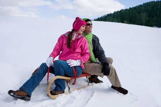 Smiling couple sitting on sled on snowy ski slope : Stock Photo