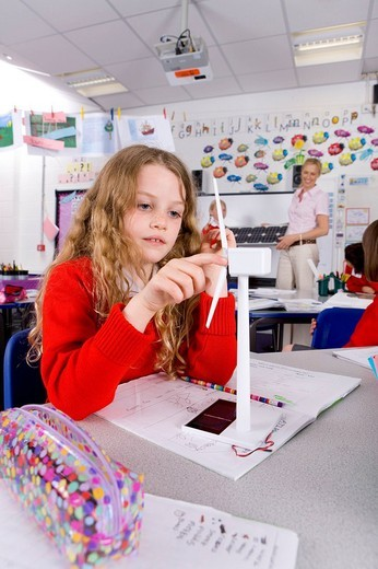 Serious school girl spinning model wind turbine in classroom : Stock Photo