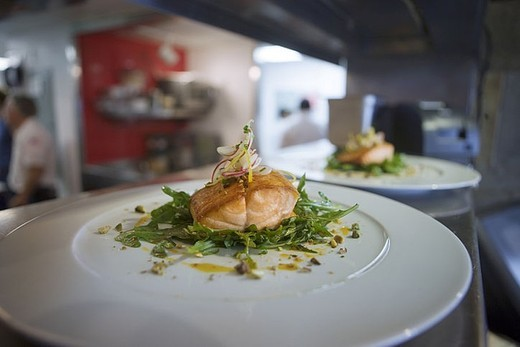 Salmon dish in commercial kitchen, close-up, focus on foreground : Stock Photo