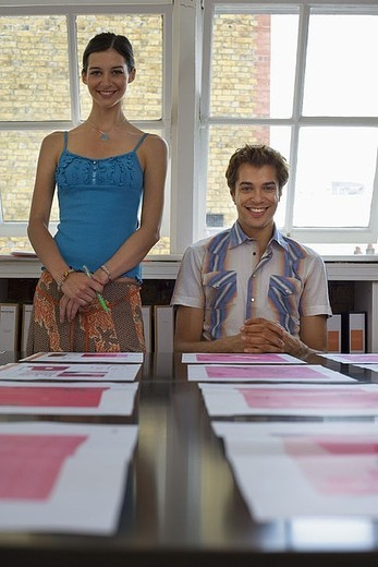 Young man and woman looking at various designs arranged on large table in office, surface level : Stock Photo