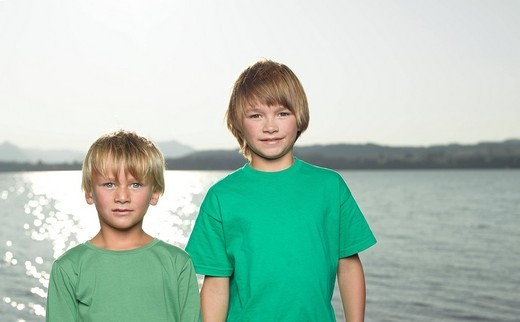 Two young boys standing beside a lake : Stock Photo