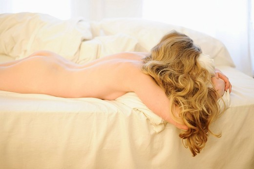 Stock Photo: 4208R-11064 A nude woman with long blonde hair lying facedown on a bed